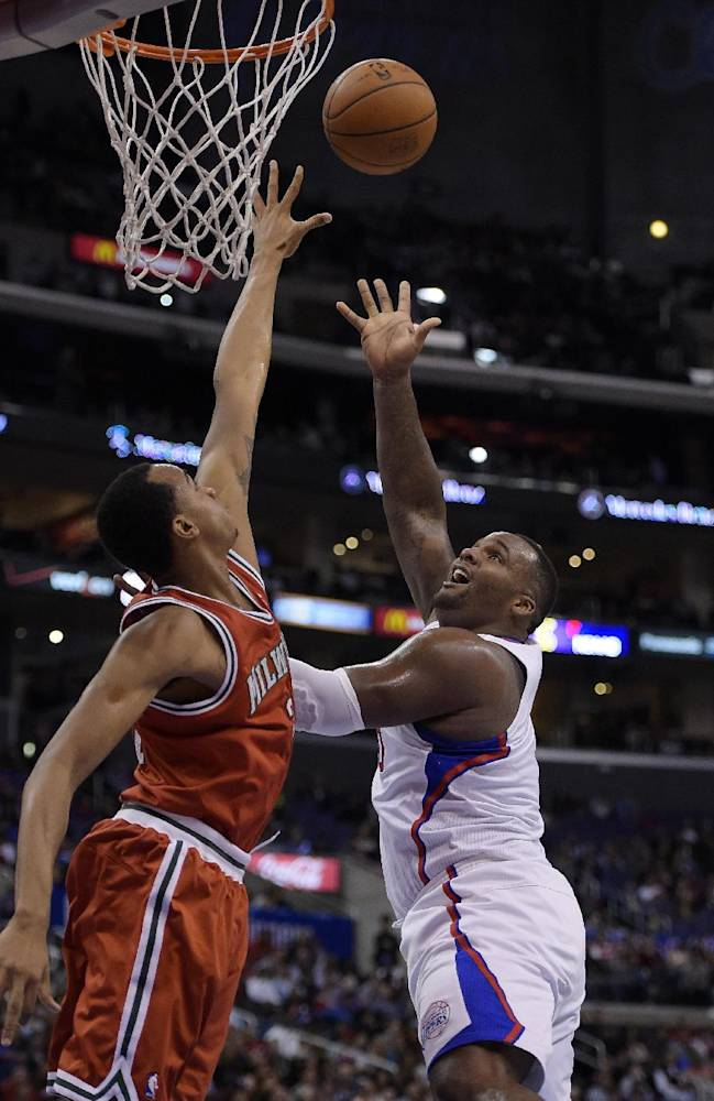 Los Angeles Clippers forward Glen Davis, right, puts yup a shot as Milwaukee Bucks center John Henson defends during the first half of an NBA basketball game, Monday, March 24, 2014, in Los Angeles