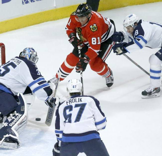 Winnipeg Jets goalie Al Montoya (35) makes a save on a shot by Chicago Blackhawks right wing Marian Hossa (81) as Michael Frolik (67) and James Wright defend during the first period of an NHL hockey game Sunday, Jan. 26, 2014, in Chicago
