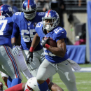 New York Giants running back Rashad Jennings (23) runs away from Arizona Cardinals' Calais Campbell (93) during the second half of an NFL football game Sunday, Sept. 14, 2014, in East Rutherford, N.J The Associated Press