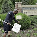 FILE - In this Monday, Sept. 8, 2014, file photo, Baltimore Ravens senior director of security Darren Sanders removes signs that were posted in support of former Ravens running back Ray Rice in front of the NFL football team's headquarters, in Owings Mills, Md. Sanders was charged, Tuesday, Dec. 30, 2014, with a sex offense and is due in court in February, according to court records. (AP Photo/Patrick Semansky, File)