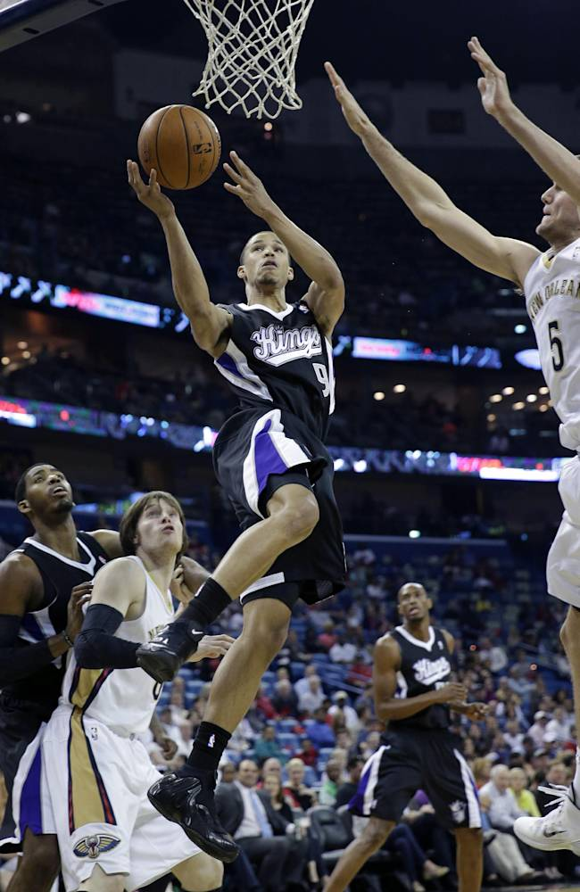 Sacramento Kings Jared Cunningham (9) goes to the basket against New Orleans Pelicans center Jeff Withey (5) and forward Luke Babbitt, second left, in the first half of an NBA basketball game in New Orleans, Monday, March 31, 2014