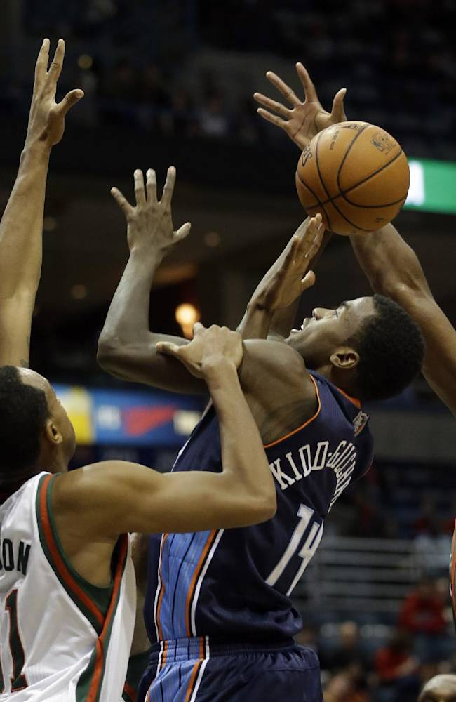 Charlotte Bobcats' Michael Kidd-Gilchrist (14) shoots between Milwaukee Bucks' John Henson (31) and Ekpe Udoh (5) during the first half of an NBA basketball game on Saturday, Nov. 23, 2013, in Milwaukee