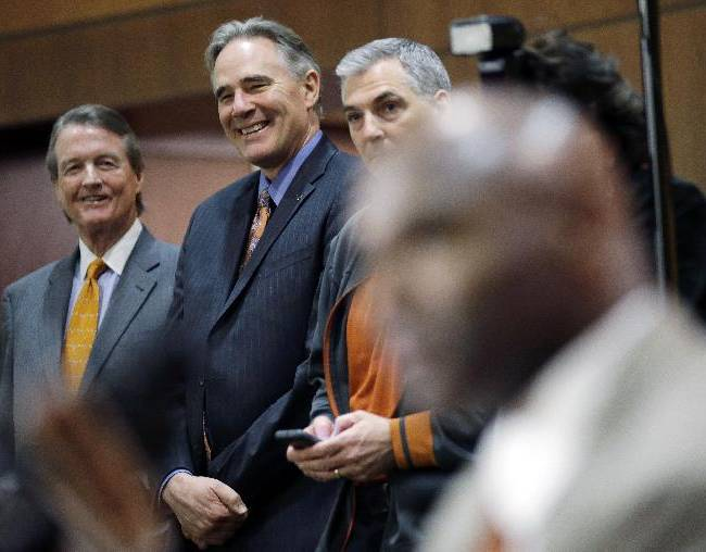 Texas president Bill Powers, left, and athletic director Steve Patterson, center, listen as Charlie Strong, right, answers questions during an NCAA college football news conference where Strong was introduced as the new Texas coach, Monday, Jan. 6, 2014, in Austin, Texas. Strong replaces Mack Brown, who coached Texas for 16 years and won the 2005 national championship. Strong spent the previous four years at Louisville