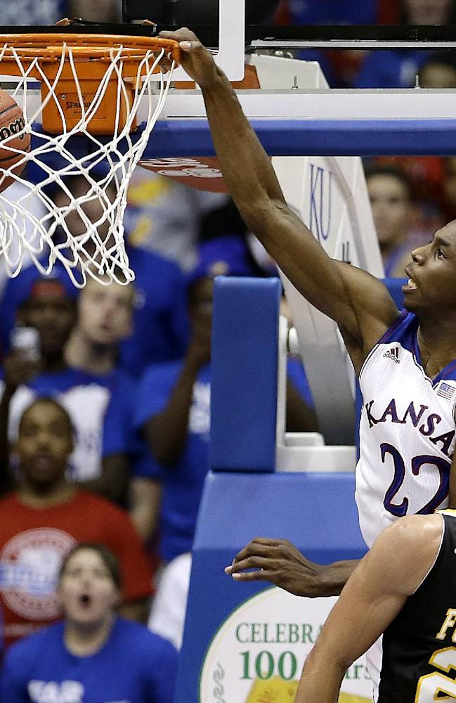 Kansas' Andrew Wiggins (22) gets past Fort Hays State's Jake Stoppel to dunk the ball during the second half of an exhibition NCAA college basketball game Tuesday, Nov. 5, 2013, in Lawrence, Kan. Kansas won the game 92-75