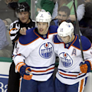 Referee Brad Watson (23) signals a goal scored by Edmonton Oilers' Taylor Hall (4) as Hall celebrates the score with Jordan Eberle (14) in the third period of an NHL hockey game against the Dallas Stars, Tuesday, Nov. 25, 2014, in Dallas. The Stars won th