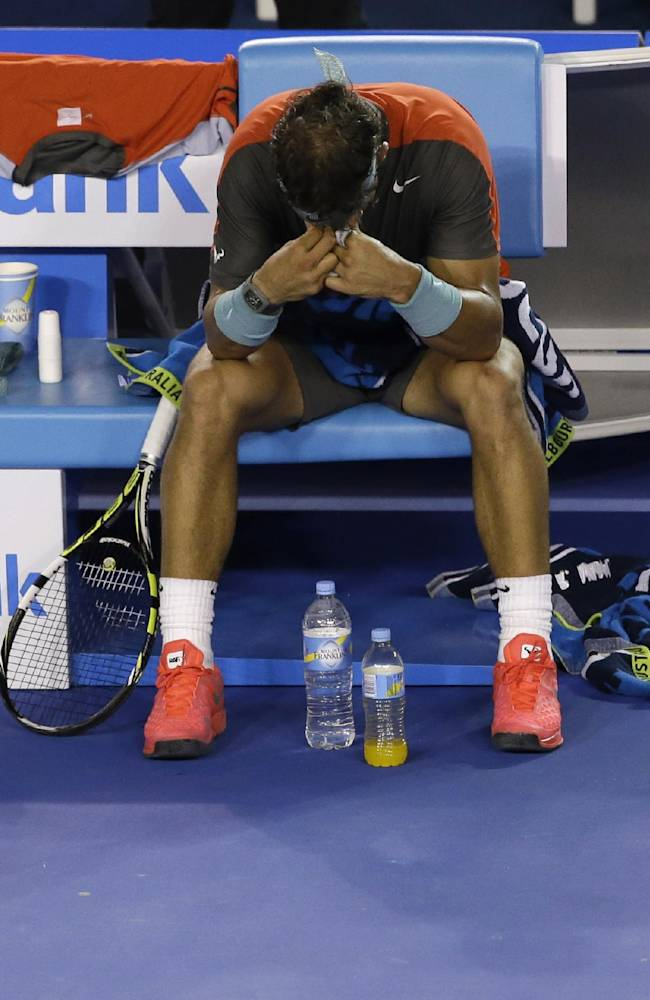 Rafael Nadal of Spain sits in a chair during a break in the men's singles final against Stanislas Wawrinka of Switzerland at the Australian Open tennis championship in Melbourne, Australia, Sunday, Jan. 26, 2014