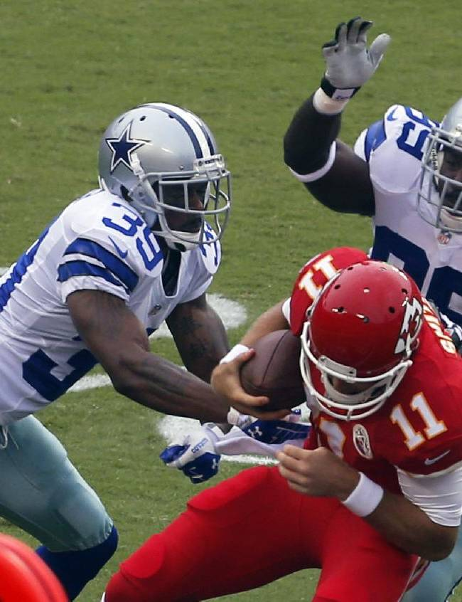 Kansas City Chiefs quarterback Alex Smith (11) is tackled by Dallas Cowboys cornerback Brandon Carr (39) and defensive end George Selvie (99) during the first half of an NFL football game at Arrowhead Stadium in Kansas City, Mo., Sunday, Sept. 15, 2013