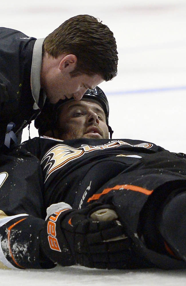 Anaheim Ducks left wing Dustin Penner is seen to by a trainer after being injured during the second period of their NHL hockey game against the Dallas Stars, Sunday, Oct. 20, 2013, in Anaheim, Calif