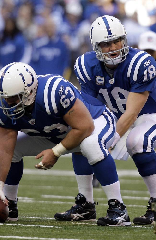 In this Nov. 1, 2009, file photo, Indianapolis Colts quarterback Peyton Manning takes the snap from center Jeff Saturday during an NFL football game against the San Francisco 49ers in Indianapolis. Saturday is torn in choosing sides for Sunday night's showdown between Manning's Broncos and his former team, like other Colts fans, is a struggle