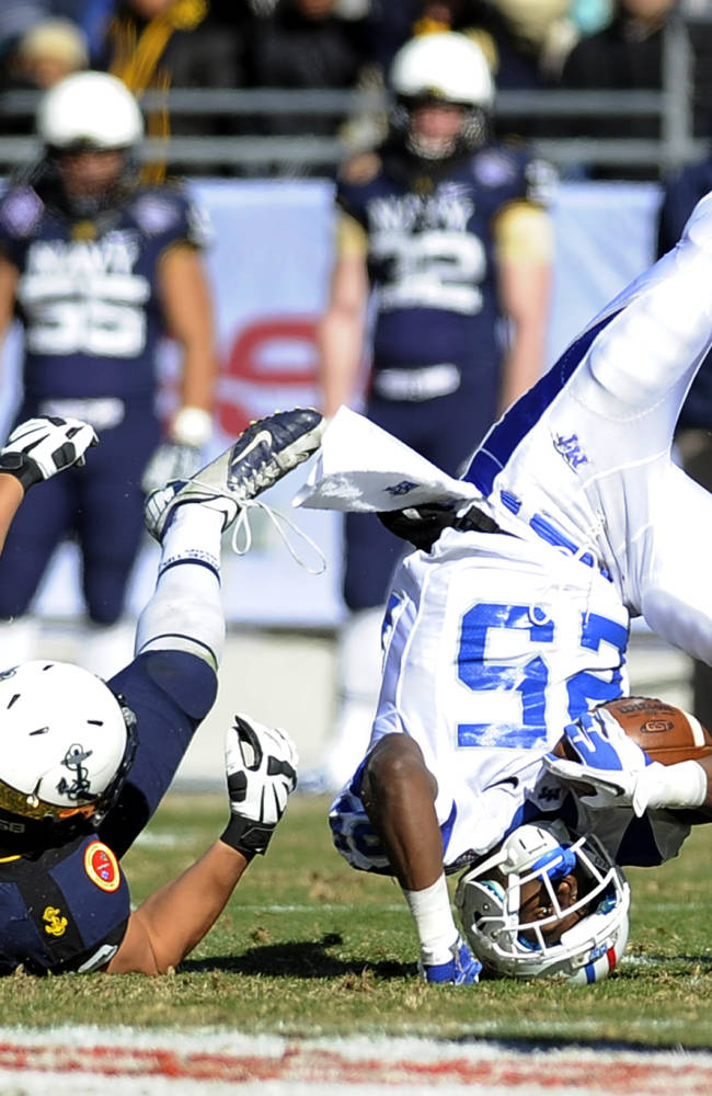 Middle Tennessee Blue Raiders running back Reggie Whatley (25) is upended by Navy Midshipmen defensive end Evan Palelei (58) on a tackled in the first half during the Armed Forces Bowl NCAA college football game, Monday, Dec. 30, 2013, in Fort Worth