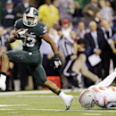 Michigan State's Jeremy Langford (33) runs out of the tackle of Ohio State's Corey Brown (3) for a 26-yard touchdown run during the fourth quarter of an Big Ten Conference championship NCAA college football game Saturday, Dec. 7, 2013, in Indianapolis. Mi