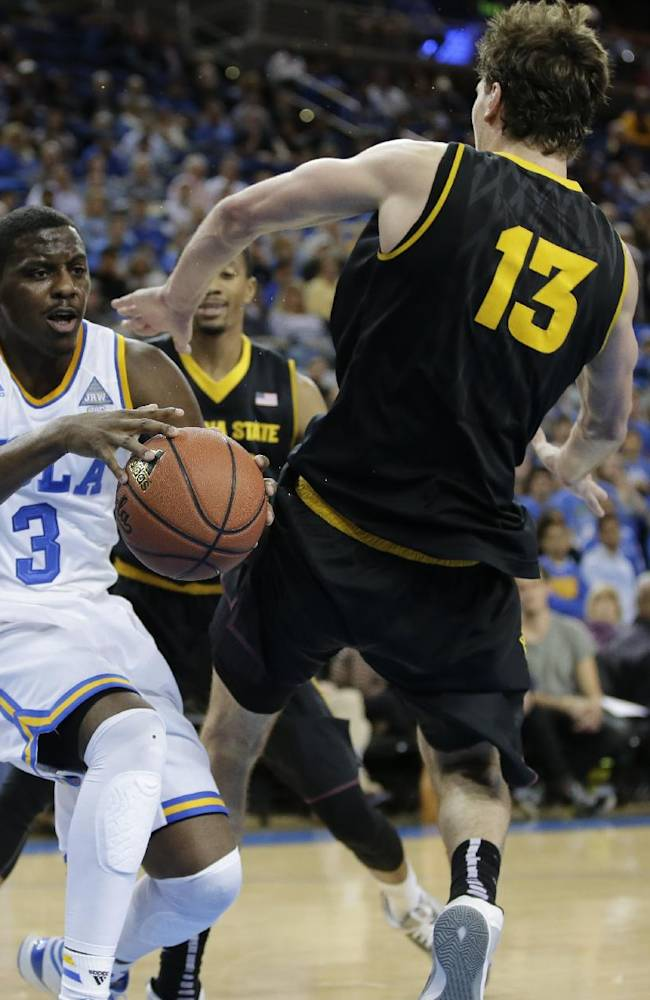 UCLA guard Jordan Adams, left, is folded by Arizona State center Jordan Bachynski during the second half of an NCAA college basketball game in Los Angeles, Sunday, Jan. 12, 2014