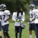 Seattle Seahawks cornerback Richard Sherman, center, and other defensive players stand on the sideline during the final day of NFL football training camp, Wednesday, Aug. 13, 2014, in Renton, Wash The Associated Press