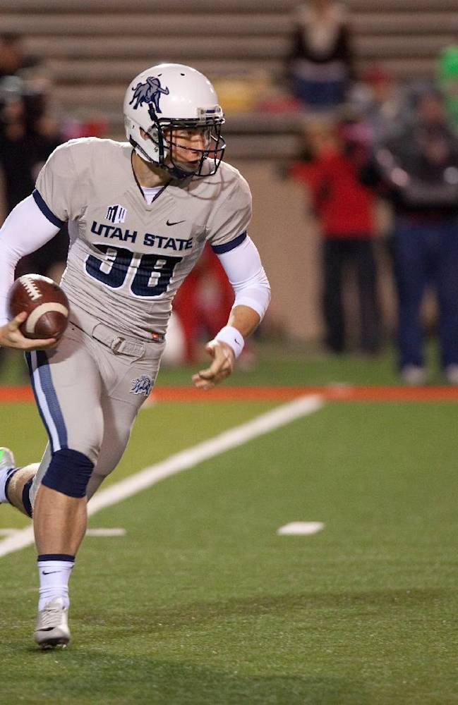Utah State punter Jaron Bentrude fakes a punt and runs for a touchdown during the second half of an NCAA college football game against Utah State, Saturday, Oct. 19, 2013, at University Stadium in Albuquerque, N.M. Utah State won 45-10