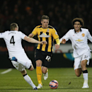 Manchester United's Phil Jones, left challenges Cambridge United's Liam Hughes for the ball during their English FA Cup fourth round soccer match between Cambridge United and Manchester United, in Cambridge, England, Friday, Jan. 23, 2015