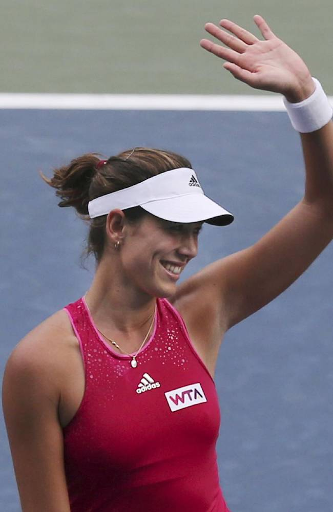 Garbine Muguruza of Spain waves after winning over Jelena Jankovic of Serbia during their second round match of the Pan Pacific Open Tennis tournament in Tokyo, Thursday, Sept. 18, 2014