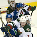 Minnesota Wild's Charlie Coyle (3) and Jared Spurgeon (46) try to clear Vancouver Canucks Daniel Sedin (22) and Alex Burrows (14) from in front of Wild goalie Devan Dubnyk (40) during the third period of NHL action in Vancouver, British Columbia, Sunday,