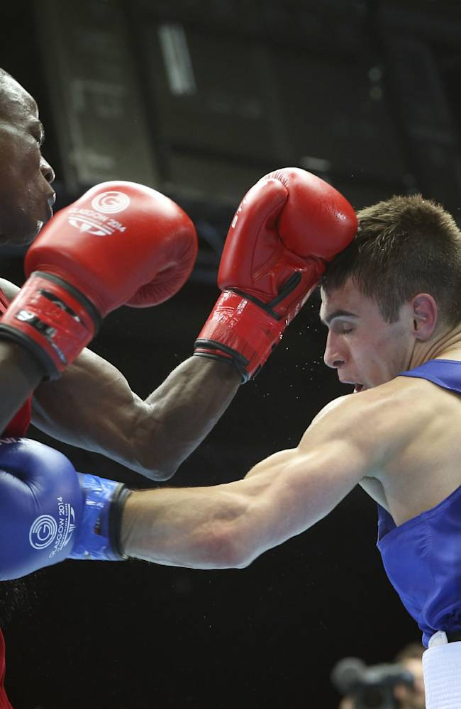 Australia's Andrew Moloney, right, lands a punch on Nigeria's Wasiu Taiwo during their men's flyweight boxing preliminary match at the Commonwealth Games Glasgow 2014, in Scotland, Sunday, July 27, 2014