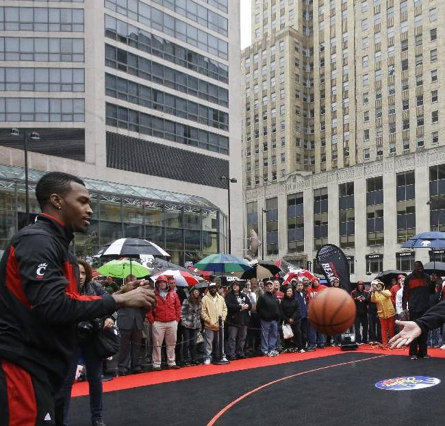 An assistant tosses a basketball to Cincinnati senior guard Sean Kilpatrick during the team's Midday Madness event to kickoff the NCAA college basketball season, Thursday, Oct. 17, 2013, at Fountain Square in downtown Cincinnati