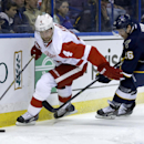 Detroit Red Wings' Jakub Kindl, left, of the Czech Republic, and St. Louis Blues' Dmitrij Jaskin, of Russia, chase a loose puck during the second period of an NHL hockey game Sunday, April 13, 2014, in St. Louis The Associated Press