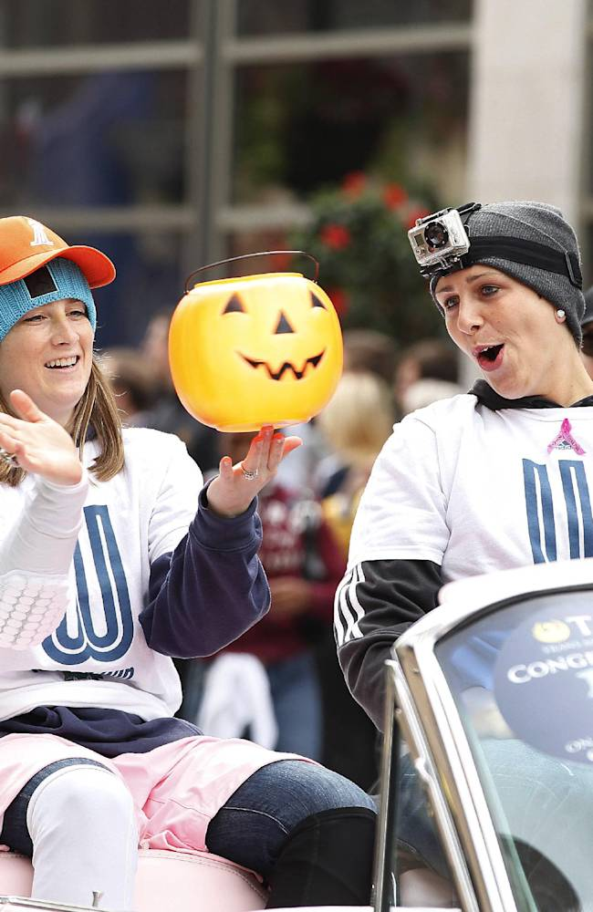 Minnesota Lynx guard Lindsay Whalen, left, spins a plastic pumpkin on her finger, as teammate forward Janel McCarville, right, cheers her on during the celebratory parade for their WNBA Championship title, Monday, Oct. 14, 2013, in Minneapolis