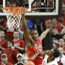 St. John's Chris Obekpa, center, attempts to block the shot of Louisville's Russ Smith during the first half of an NCAA college basketball game, Thursday, Feb. 14, 2013, in Louisville, Ky. (AP Photo/Timothy D. Easley)
