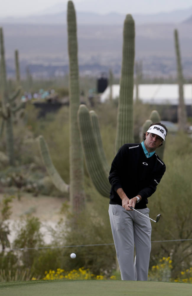 Bubba Watson chips to the 10th green against Mikko Ilonen, of Finland, during the first round of the Match Play Championship golf tournament on Wednesday, Feb. 19, 2014, in Marana, Ariz