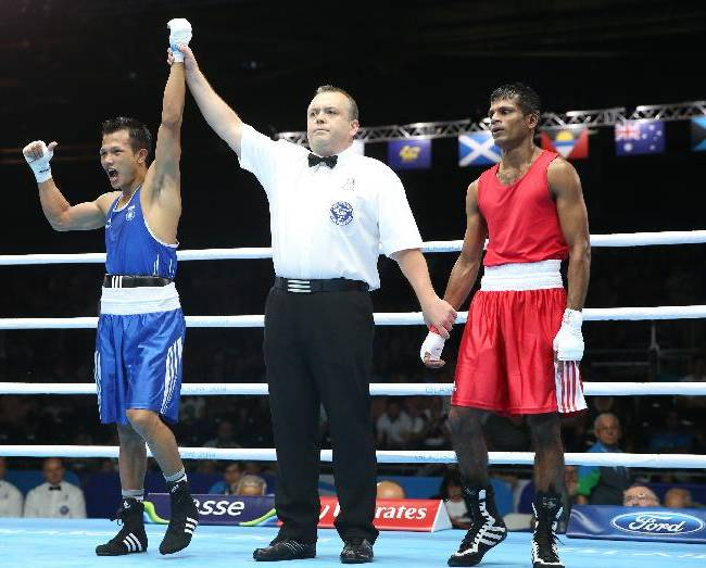 India's Devendro Laishram, left, celebrates after defeating Sri Lanka's Madushan Gamage  in the Men's light flyweight preliminaries round bout at the Commonwealth Games Glasgow 2014, in Glasgow Scotland, Monday July 28, 2014