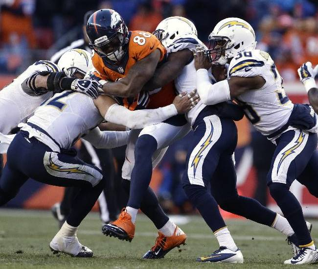 Denver Broncos wide receiver Demaryius Thomas (88) is wrapped up by the San Diego Chargers defense in the third quarter of an NFL AFC division playoff football game, Sunday, Jan. 12, 2014, in Denver