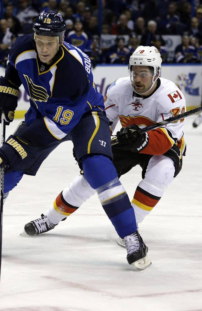 St. Louis Blues' Jay Bouwmeester, left, looks to pass against Calgary Flames' T.J. Galiardi during the first period of an NHL hockey game Thursday, Nov. 7, 2013, in St. Louis