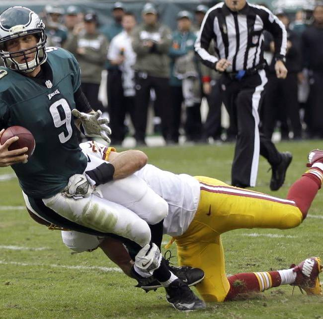 Philadelphia Eagles quarterback Nick Foles (9) is sacked by Washington Redskins strong safety Reed Doughty during the first half of an NFL football game in Philadelphia, Sunday, Nov. 17, 2013