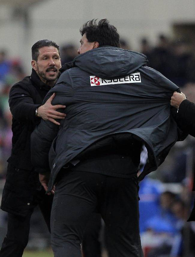 Atletico's assistant coach, German Burgos, centre, talks with the referee, left, as Atletico's coach Diego Simeone from Argentina, second left, holds him  during a Spanish La Liga soccer match between Atletico de Madrid and Real Madrid at the Vicente Calderon stadium in Madrid, Spain, Sunday, March 2, 2014