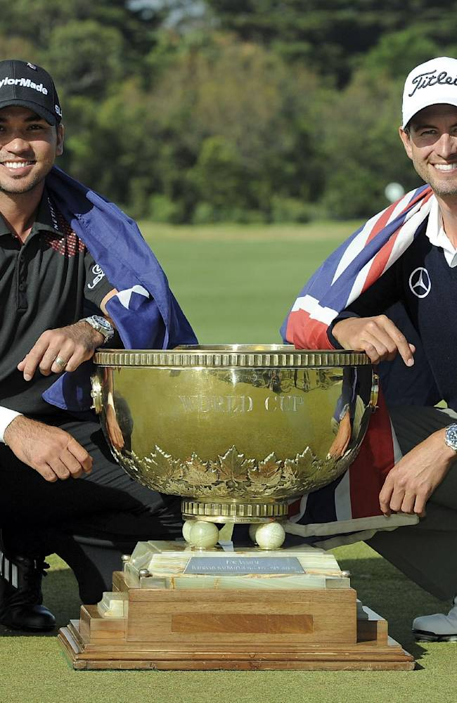 Jason Day, left of Australia and compatriot Adam Scott draped in their national flags with the World Cup of Golf trophy after winning the team event at Royal Melbourne Golf Course in Australia, Sunday, Nov. 24, 2013