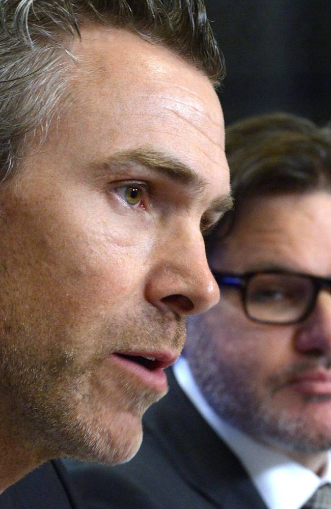 Former Vancouver Canucks captain Trevor Linden, left, speaks at a press conference as team owner Francesco Aquilini looks on in Vancouver on Wednesday, April 9, 2014. Linden has been hired as Vancouver's president of hockey operations