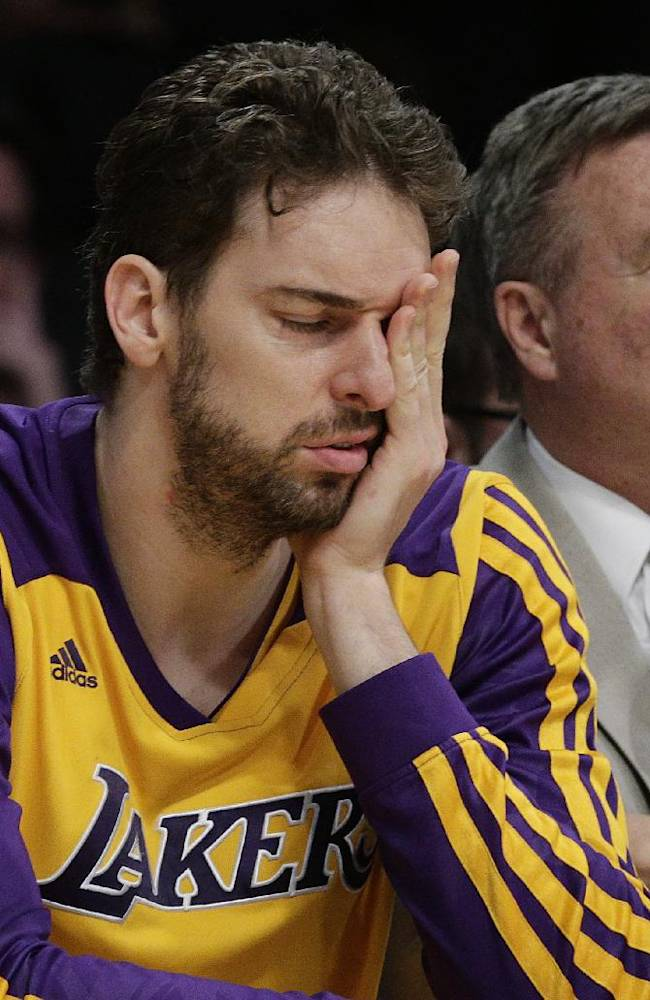 Los Angeles Lakers' Pau Gasol, of Spain, covers his face while sitting on the bench during the second half of an NBA basketball game against the Los Angeles Clippers on Thursday, March 6, 2014, in Los Angeles. The Clippers won 142-94
