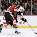 Chicago Blackhawks left wing Bryan Bickell, left, checks Philadelphia Flyers right wing Pierre-Edouard Bellemare, as Bellemare takes a shot on goal during the first period of an NHL hockey game Tuesday, Oct. 21, 2014, in Chicago The Associated Press