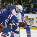 Tampa Bay Lightning's Nikita Kucherov, center, of Russia, controls the puck against New York Rangers' John Moore, left, and J.T. Miller (10) during the first period of an NHL hockey game Monday, Dec. 1, 2014, in New York The Associated Press