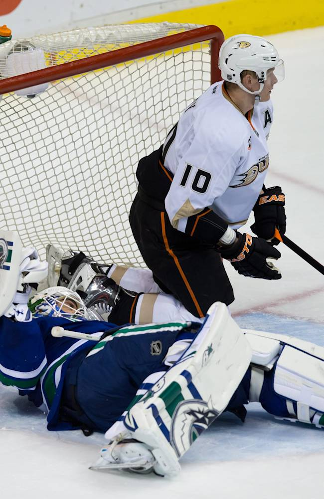 Vancouver Canucks goalie Eddie Lack, left, of Sweden, lies on the ice after Anaheim Ducks' Corey Perry was pushed into him by Canucks' Jason Garrison, not pictured, during the second period of an NHL hockey game Saturday, March 29, 2014, in Vancouver, British Columbia