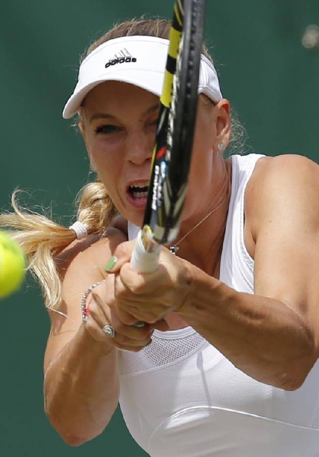 Caroline Wozniacki of Denmark plays a return to Ana Konjuh of Croatia during their women's singles match at the All England Lawn Tennis Championships in Wimbledon, London, Friday, June 27, 2014