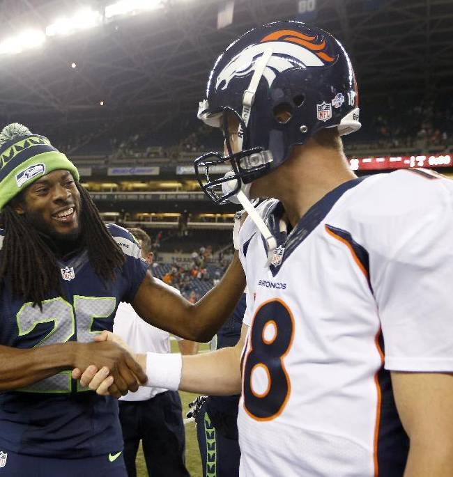 In this photo taken Aug. 17, 2013, Seattle Seahawks cornerback Richard Sherman, (25) shakes hands with Denver Broncos quarterback Peyton Manning, right, after the Seahawks beat the Broncos 40-10, in a preseason NFL football game in Seattle. The two teams square off in Super Bowl XLVIII on Sunday, Feb. 2, 2014, in East Rutherford, N.J