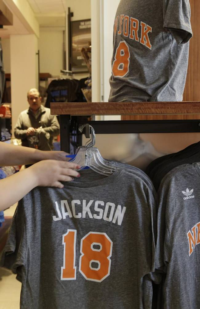 A New York Knicks store employee arranges Phil Jackson t-shirts prior to a news conference where he was introduced as the new president of the New York Knicks, Tuesday, March 18, 2014 in New York. Jackson, who won two NBA titles as a player with the Knicks, also won 11 championships while coaching the Chicago Bulls and the Los Angeles Lakers