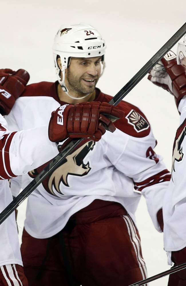 Phoenix Coyotes' Zbynek Michalek, right, from the Czech Republic, celebrates his overtime goal with teammates Kyle Chipchura, center, and Oliver Ekman-Larsson, from Sweden, during an NHL preseason hockey game, Wednesday, Sept. 25, 2013, in Calgary, Alberta. The Coyotes won 3-2