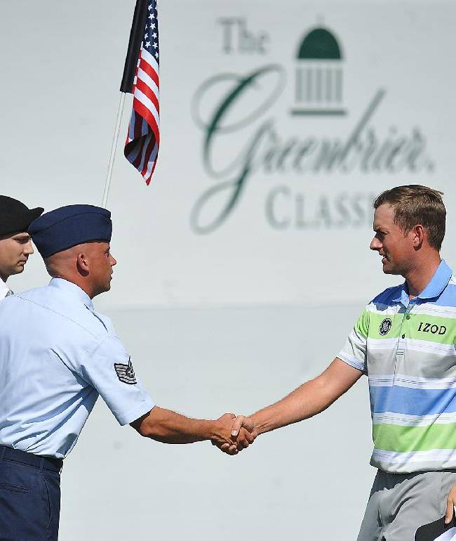 Golfer Webb Simpson, right, shakes hands with West Virginia Air National Guard TSGT Kevin Cordel during the second round of the Greenbrier Classic golf tournament at the Greenbrier Resort in White Sulphur Springs, W.Va., Friday, July 4, 2014