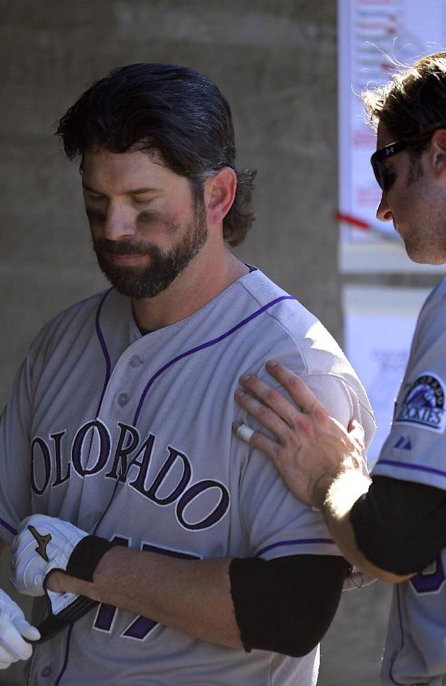 Colorado Rockies' Todd Helton, left, gets a pat from Charlie Blackmon after striking out in the ninth inning of the Rockies' baseball game against the Los Angeles Dodgers, Sunday, Sept. 29, 2013, in Los Angeles