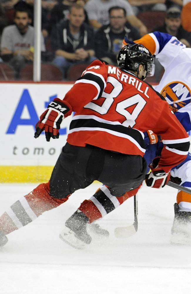 New York Islanders' Josh Bailey, right, takes a shot past New Jersey Devils' Jon Merrill during the first period of a preseason NHL hockey game, Thursday, Sept. 19, 2013, in Newark, N.J