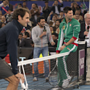 Micromax Indian Aces player Roger Federer, left, and Musafir.com UAE Royals Novak Djokovic sit on the net during a match with Indian Bollywood actors, on the sidelines of the International Premier Tennis League, in New Delhi, India, Monday, Dec. 8, 2014. (AP Photo /Manish Swarup)