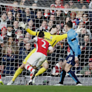 Arsenal's Laurent Koscielny, left, heads the ball in to score the opening goal during their English Premier League soccer match between Arsenal and Stoke City at the Emirates stadium in London, Sunday, Jan. 11, 2015