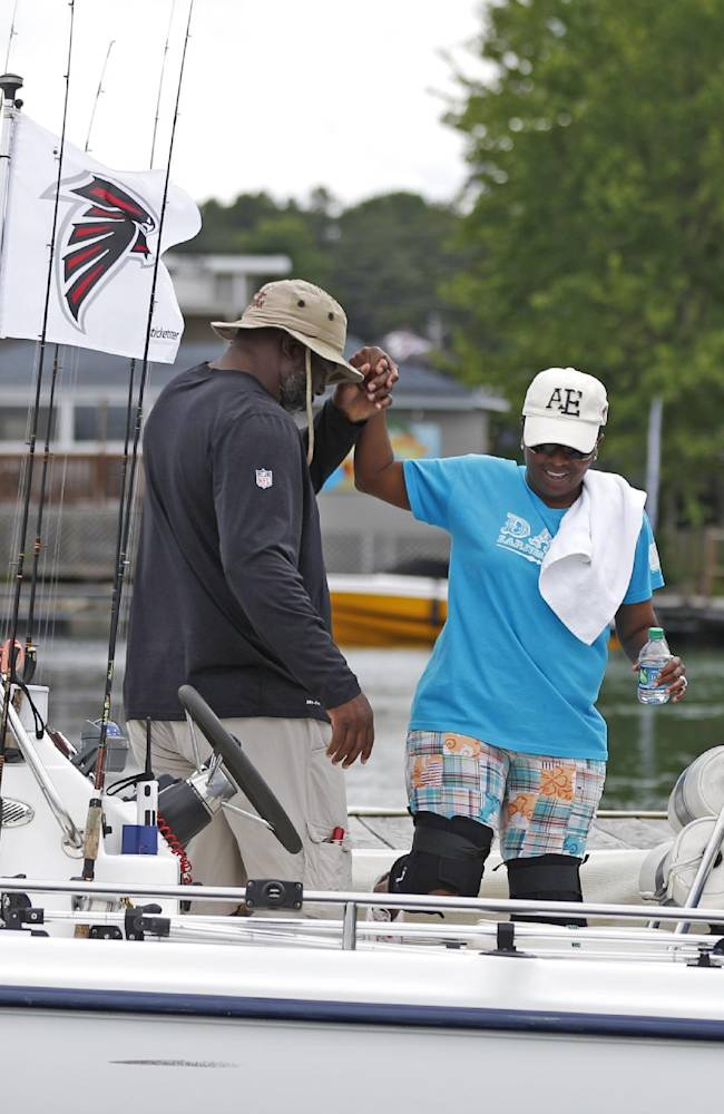 Atlanta Falcons defensive line coach Bryan Cox, helps U.S. Army veteran Kimberly Maybin into a boat as they prepare to depart on team's annual 'Fishing With the Falcons' event for wounded veterans Wednesday,  June 11, 2014, on Lake Lanier in Buford, Ga. The Falcons host the annual out outing to thank wounded veterans. The veterans get a chance to meet and fish with players, coaches and cheerleaders