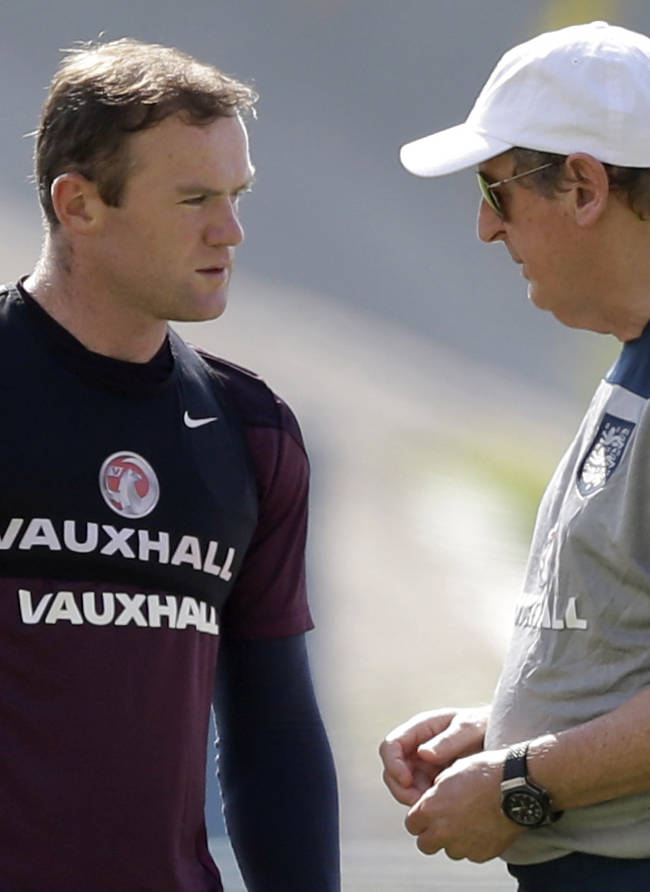 This is a Monday, June 16, 2014   file photo of England national soccer team coach Roy Hodgson, right,  as he speaks with Wayne Rooney during a squad training session for the 2014 soccer World Cup at the Urca military base in Rio de Janeiro, Brazil.  Wayne Rooney was named England captain on Thursday, Aug. 28, 2014  taking over the leadership role of an inexperienced team in a rebuilding phase following its worst-ever World Cup