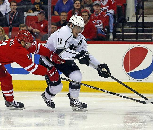 Los Angeles Kings' Anze Kopitar, right, of Slovenia, drives past Carolina Hurricanes' Jordan Staal during the first period of an NHL hockey game, Friday, Oct. 11, 2013, in Raleigh, N.C